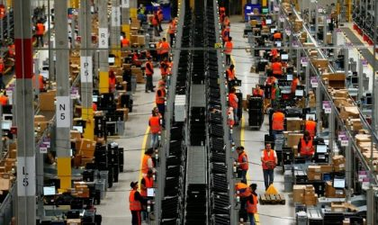 Employees handle packages in the new Amazon logistic center in Dortmund